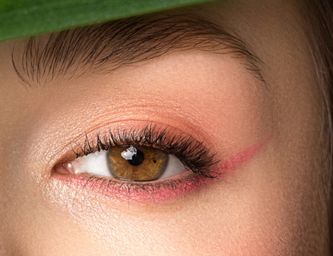 Ein braunes Auge mit einem pinken Lidschatten-Strich am unteren Wimpernkranz