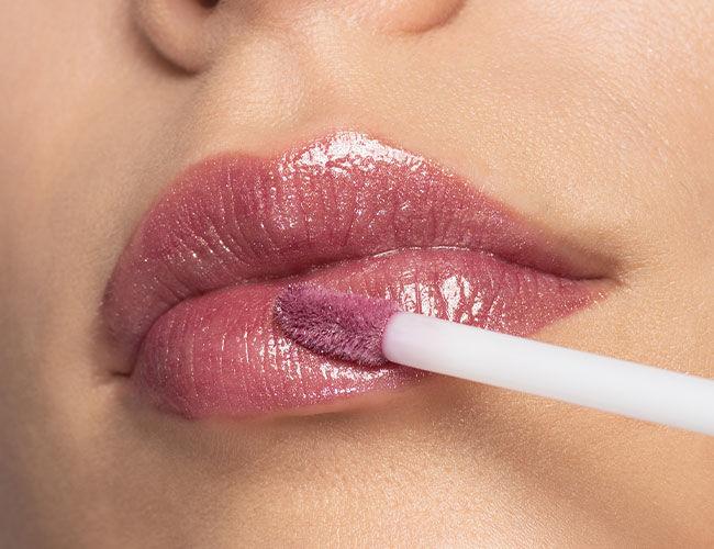 Ein rose-farbiger Lip Gloss wird auf die Lippen aufgetragen