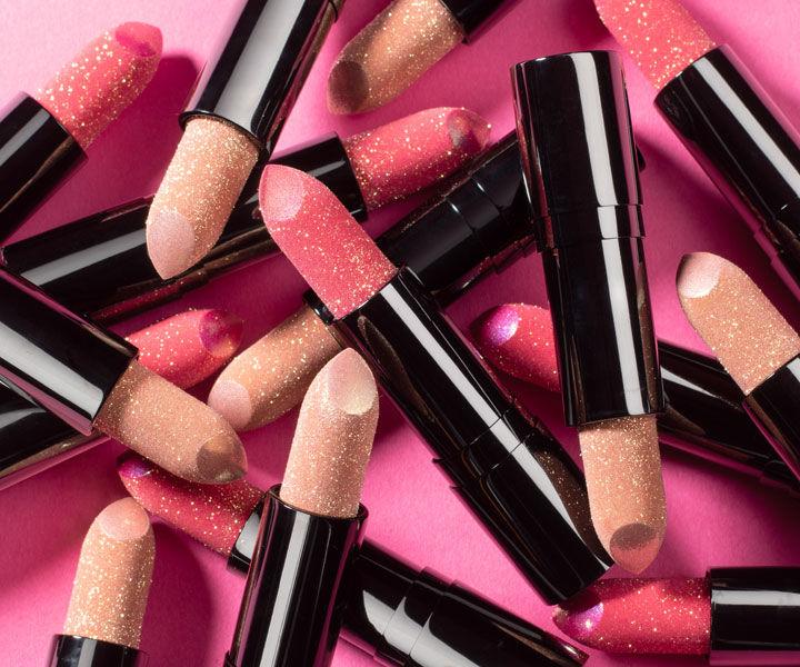 Mehrere Lip Jewels von Artdeco liegen auf einem pinken Hintergrund