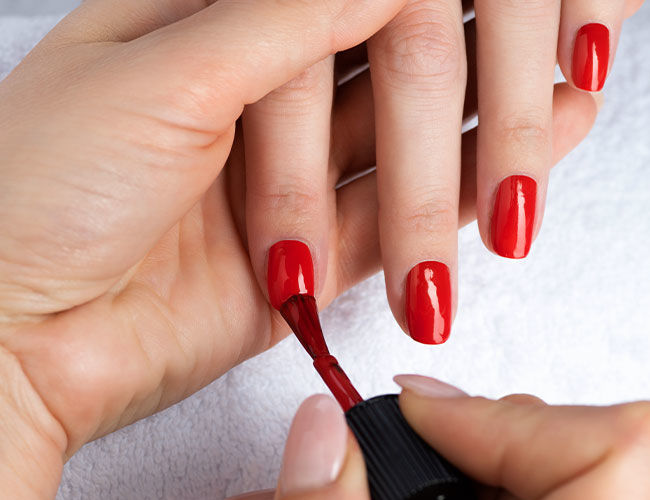 Red nail polish is applied
