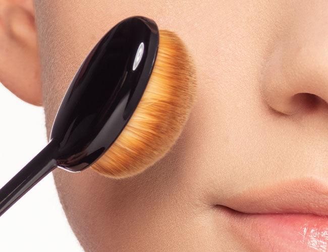 Ein Make-up Pinsels wird an eine Wange gehalten