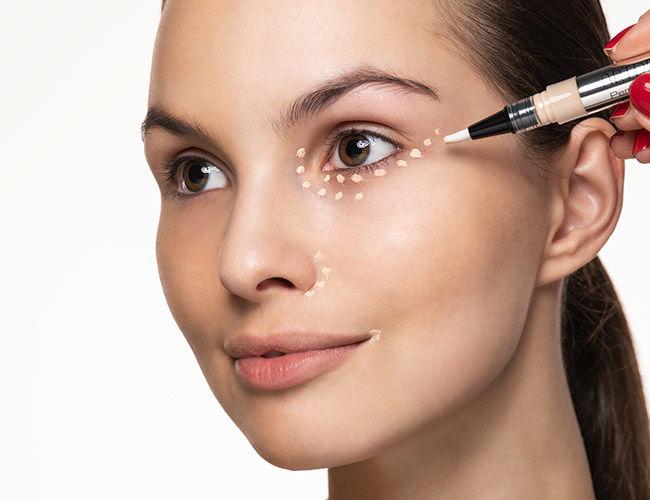 Ein Concealer wird in Pünktchen unter den Augen, an den Nasenflügeln und am Mundwinkel aufgetragen.
