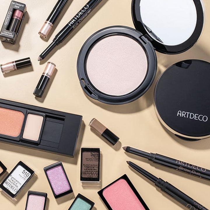 Auf einem hellen Untergrund liegen mehrere Make-Up Produkte von Artdeco