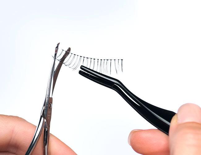Die Bandwimpern werden mit einer Schere auf die richtige Größe angepasst