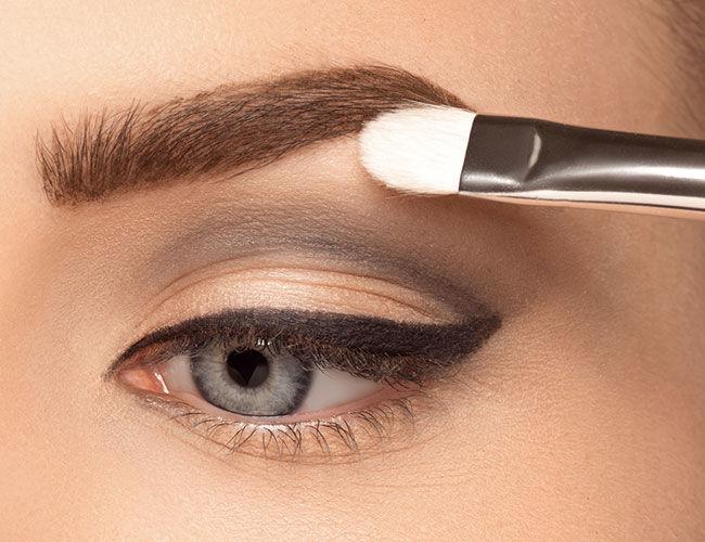 Ein heller Lidschatten wird unter den Augenbrauen aufgetragen