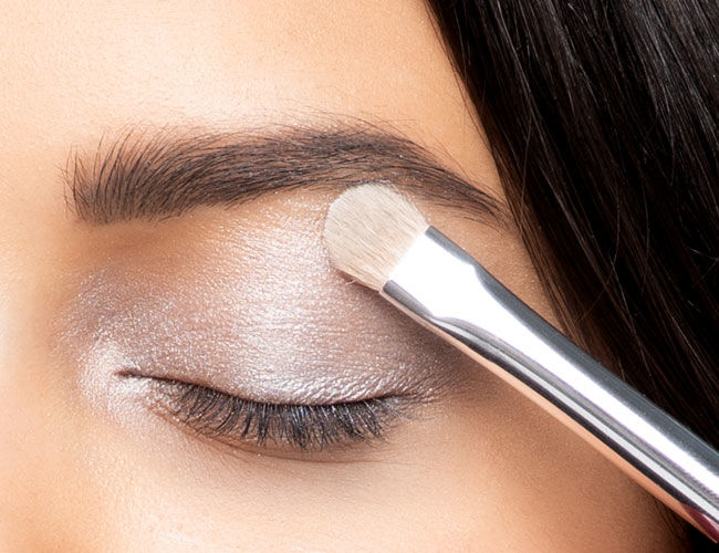 A light-colored eyeshadow is applied to the lid
