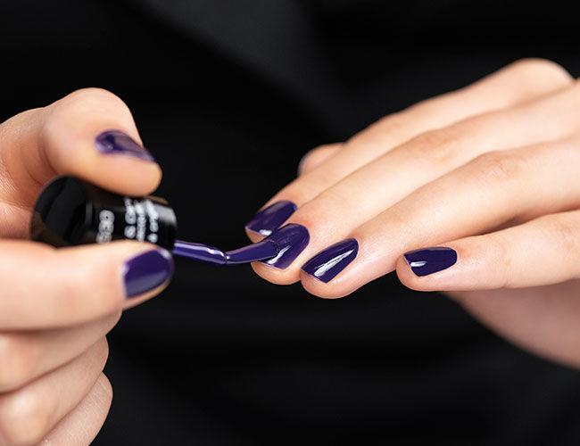 Ein violetter Nagellack wird aufgetragen