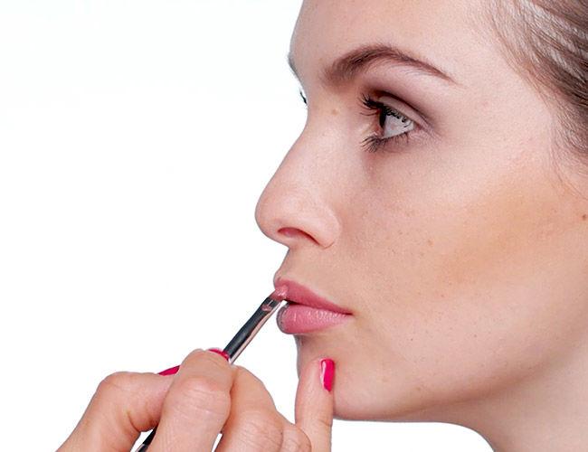 Es wird ein Lippenstift mit einem Lippenpinsel aufgetragen.