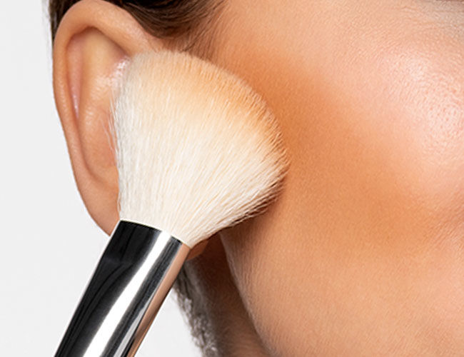 Bronzer is applied to a cheekbone with a brush