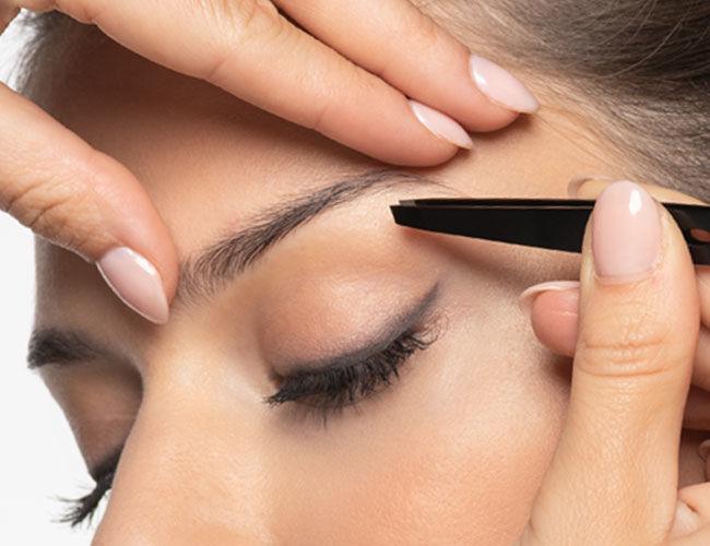 Eine Augenbrauen Pinzette wird vor ein Gesicht gehalten