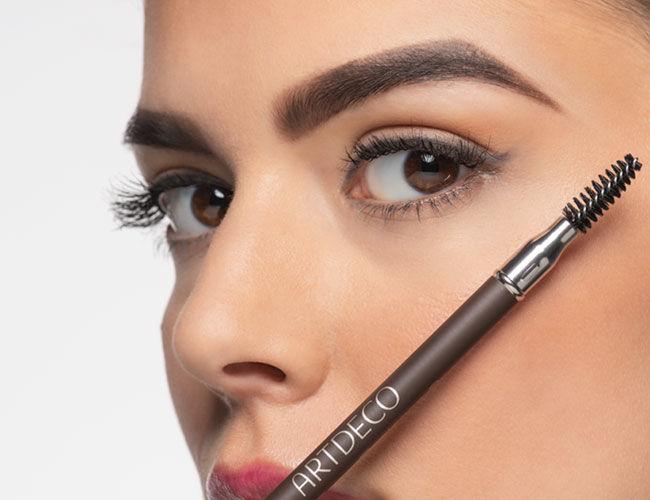 Ein Augenbrauen-Bürstchen wird vor ein Gesicht gehalten